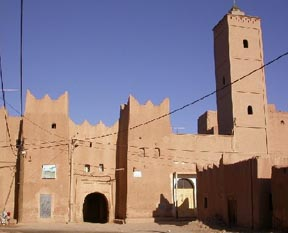 Big door and minaret of the mosque in Ksar El Khorbat.